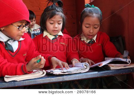 """KATHMANDU, NEPAL - JANUARY 1: Pupil in learning session during lesson in small primary school """"Happy Home School"""" in poor area of city, January 1, 2009 in Kathmandu, Nepal."""