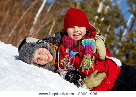 Happy friends in winterwear looking at camera while playing outside