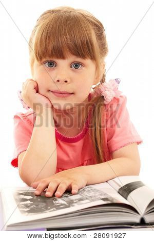 Portrait of cute girl looking at camera while reading interesting book
