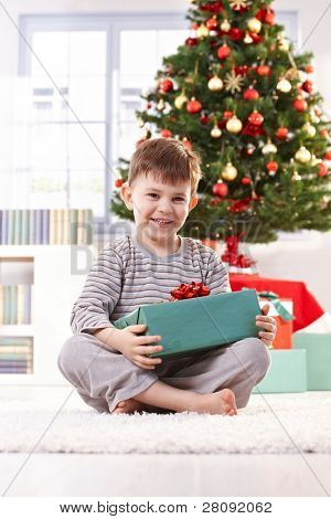 Laughing boy sitting on floor with wrapped christmas present in morning light.?