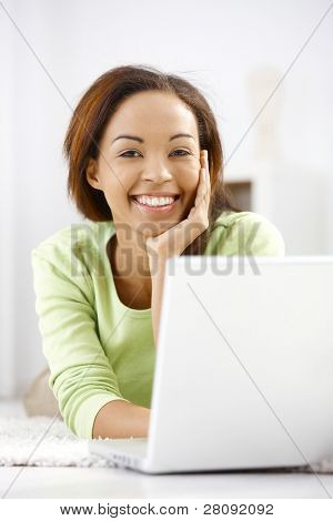 Portrait of laughing ethnic girl lying on floor, using laptop computer, looking at camera happily.?