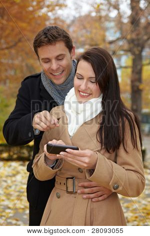 Happy couple in autumn using a smartphone