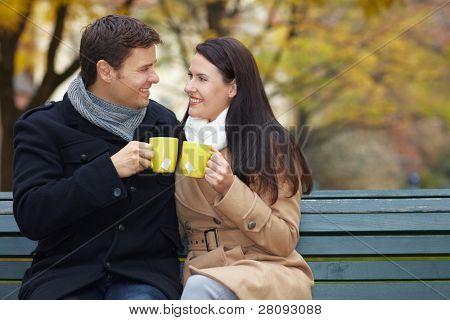 Hombre y mujer clink gafas con té caliente en otoño