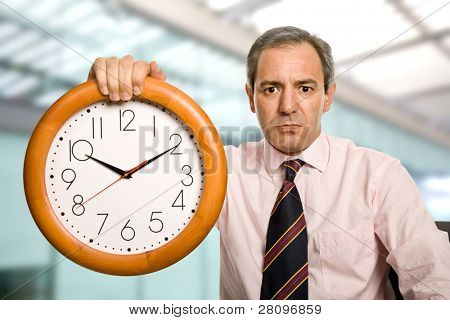 mature handsome business man holding a clock