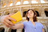 Young Female Traveler Making Selfie Photo Standing The Colosseum In Rome, Italy. Sightseeing Tour In poster