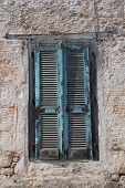 Wooden window shutters on an old stone building at Emborio on the Greek island of Halki.