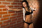 stock photo of underthings  - Young sexy woman against brick wall - JPG