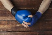Mans Hand In Boxing Bandages Holds A Hand In A Boxing Glove On A Wooden Background. Ready Gesture. T poster