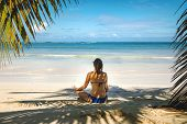 Girl Doing Yoga On Tropical Beach. Young Girl Traveler Relaxing In Vacation.girl In Yoga Position Re poster