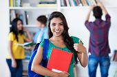 Successful Latin American Female Student With Group Of Students At Library Of University poster