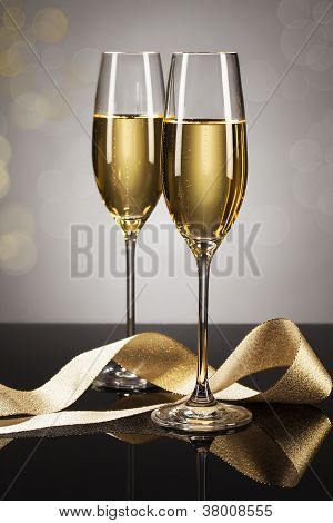 two glasses of champagne with a golden ribbon