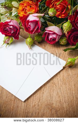 Bouquet Of Roses And White Cardboard On A Wooden Board