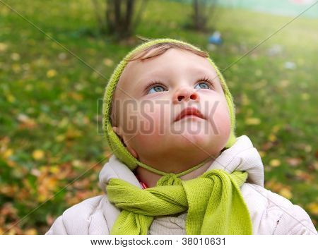 Fun Baby Looking Up With Serious Thinking Face Outdoor. Closeup Portrait On Autumn