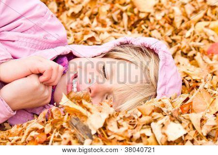 Little Girl Lying In Autumn Leaves