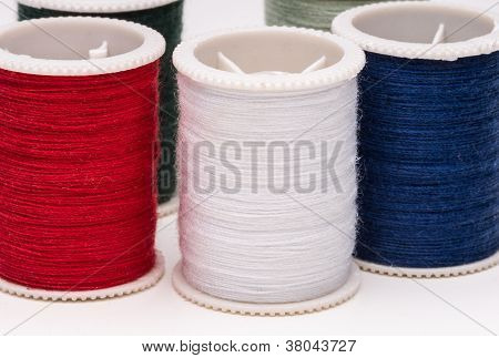 Colored Spools Of String On White Background.