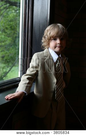 Natural Light Portrait Of Boy In Suit At The Window