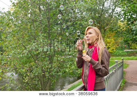 Young pretty woman Blowing soap Bubbles In The Park