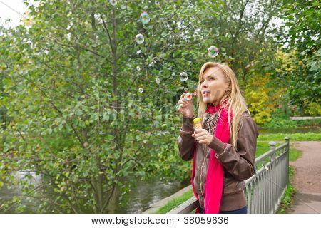 Joven bonita mujer soplar burbujas de jabón en el Parque