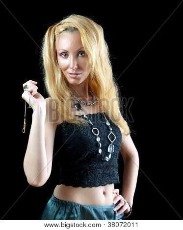 beautiful young blonde woman with long hair and jewellry on dark background.