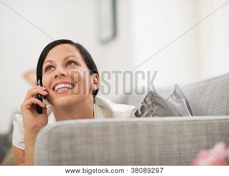 Happy Young Woman Laying On Sofa And Speaking Mobile Phone