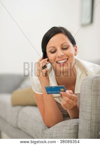 Happy Young Woman On Sofa Holding Credit Card And Speaking Mobile Phone