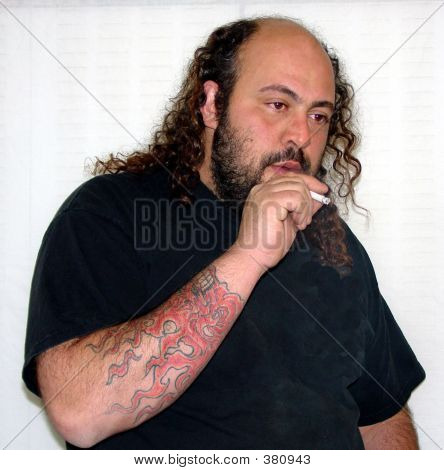 Balding man with beard and tattoo, smoking a cigarette