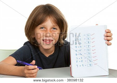 Cute Kid Showing Notebook With Math Problems.