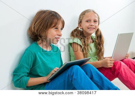 Dois miúdos sentados com Laptop e Tablet Digital.
