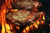 picture of flame-grilled  - Two Juicy stakes grilling on the barbecue with lots of flame licking around them