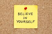 pic of slogan  - Believe In Yourself written on an yellow sticky note on a cork bulletin board - JPG