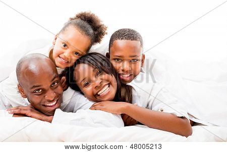 Beautiful family portrait lying in bed and smiling - isolated over white
