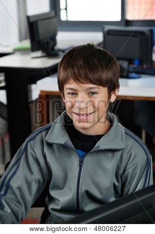 Portrait of happy teenage schoolboy sitting in computer class