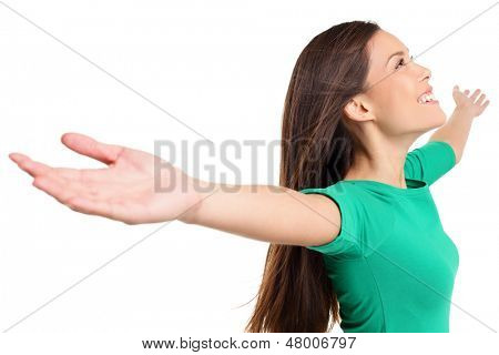 Free happy elated woman with arms out raised up in serene joyful pose. Girl in green shirt isolated on white background in studio. Mixed race Asian Caucasian female model.