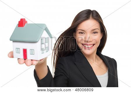 Real estate agent selling home holding mini house. Female realtor in business suit showing model house smiling happy isolated on white background. Multiracial Caucasian / Chinese Asian woman agent.