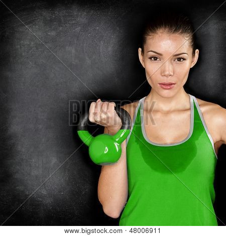 Fitness woman exercising holding kettlebell strength training biceps. Beautiful sweaty fitness instructor on blackoard background looking intense at camera. Asian Caucasian female model.
