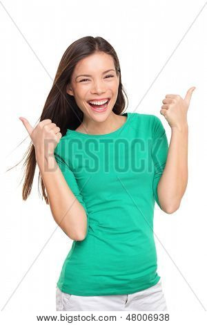 Thumbs up happy excited woman isolated on white background in green t-shirt. Cheerful joyful and elated girl looking at camera. Multiracial Asian Caucasian girl in her twenties.