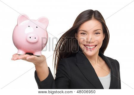 Businesswoman holding piggy bank - savings concept. Business woman or bank employee smiling happy. Female holding pink piggy bank isolated on white background. Multiracial Chinese Asian / Caucasian.