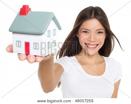 Home / house. Buying new home concept - woman holding mini house. House mortgage and happy home owner conceptual image with multi-ethnic Asian Chinese / Caucasian female model on white background.