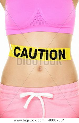 Stomach health concept showing woman belly CAUTION sign. Take care of your body, food poisoning or other concept. Conceptual healthy lifestyle image.