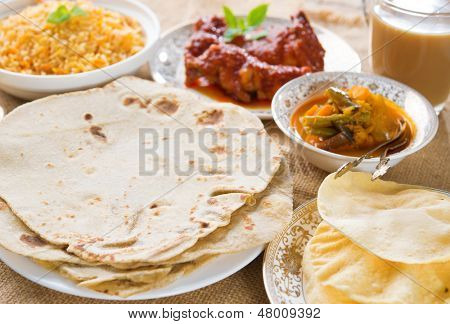 Chapatti roti or Flat bread, curry chicken, biryani rice, salad, masala milk tea and papadom. Indian food on dining table.