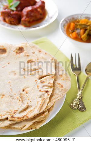 Chapatti roti or Flat bread, curry chicken and dhal. Indian food on dining table.