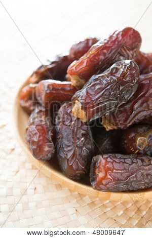 Dates fruit. Pile of fresh dried date fruits in a wooden plate.