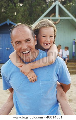 Portrait of father giving daughter piggyback ride on beach