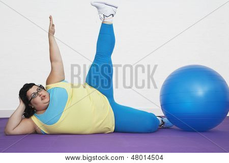 Overweight woman lying by exercise ball stretching arm and leg upwards at healthclub