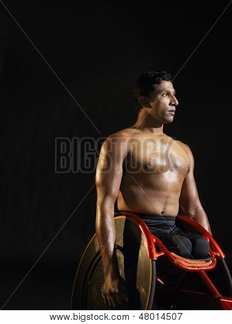 Shirtless paraplegic cycler against black background