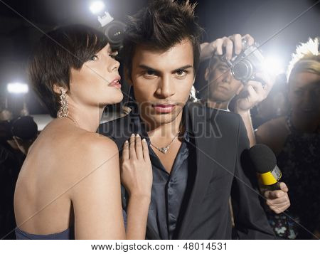 Portrait of young celebrity couple surrounded by paparazzi
