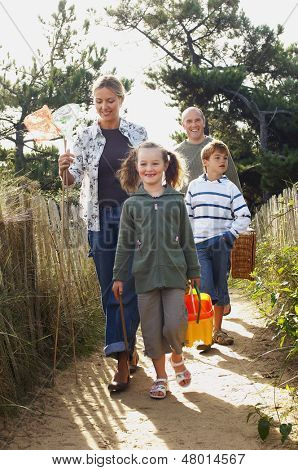Vacationing family walking on track to beach