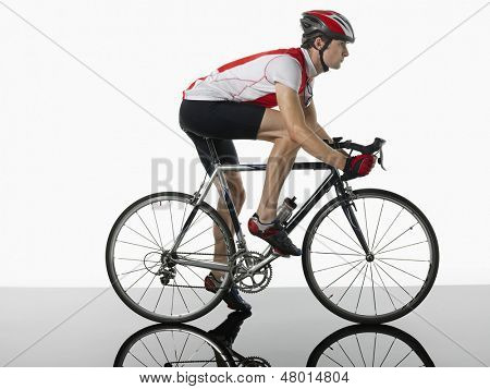 Side view of a bicyclist mounted on bicycle against white background