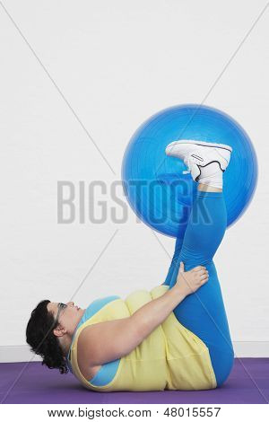Side view of an overweight woman lying down and holding up exercise ball with legs