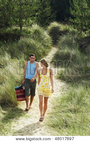 Full length of a young couple walking on trail to beach